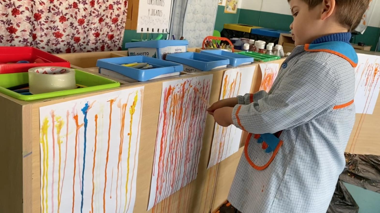 Niño de 4 años pintando de color naranja con un cuentagotas sobre un folio blanco colgado en vertical en un aula de educación infantil