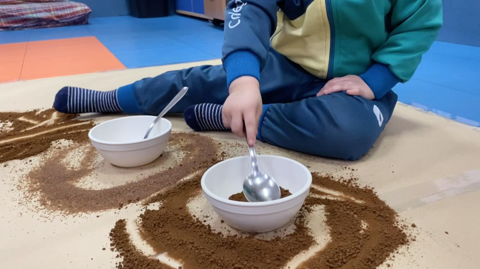 Niño de tres años sentado en el suelo de su clase jugando con una cuchara y cuencos con café y azúcar moreno