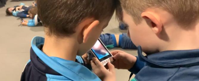 Contaplano de dos niños con las cabezas pegadas mirando juntos la pantalla de una cámara de fotos digital