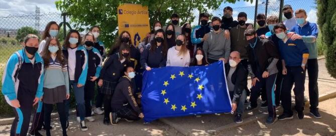 Grupo de Alumnos y alumnas del Colegio Ártica portando una bandera de Europa en el patio del colegio