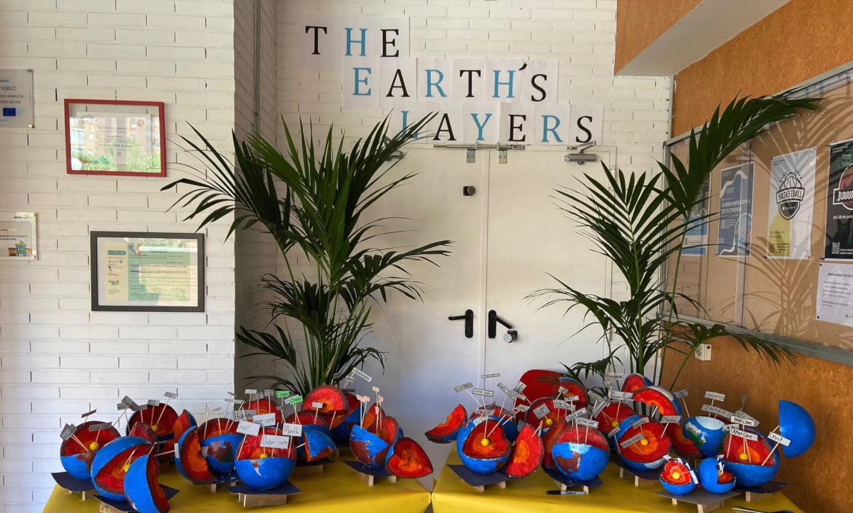 """Exposición escolar sobre las capas del planeta tierra. Maquetas del planeta tierra y sus capas sobre una mesa con un cartel en inglés que dice """"The earth layers"""" con plantas decorativas de fondo"""